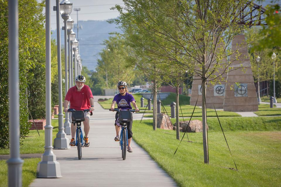 Two people riding bikes through Chattanooga on a trail.