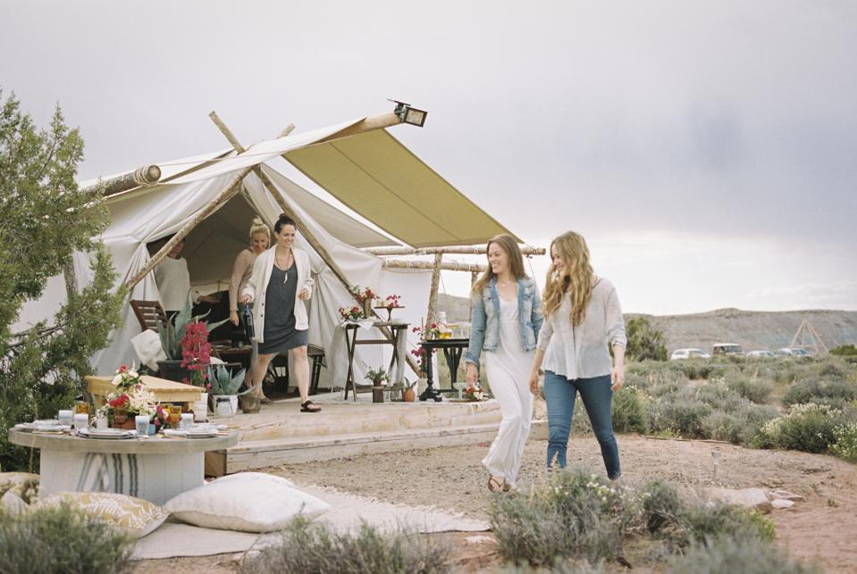 Group of friends glamping enjoying an outdoor meal, a tent in the background.