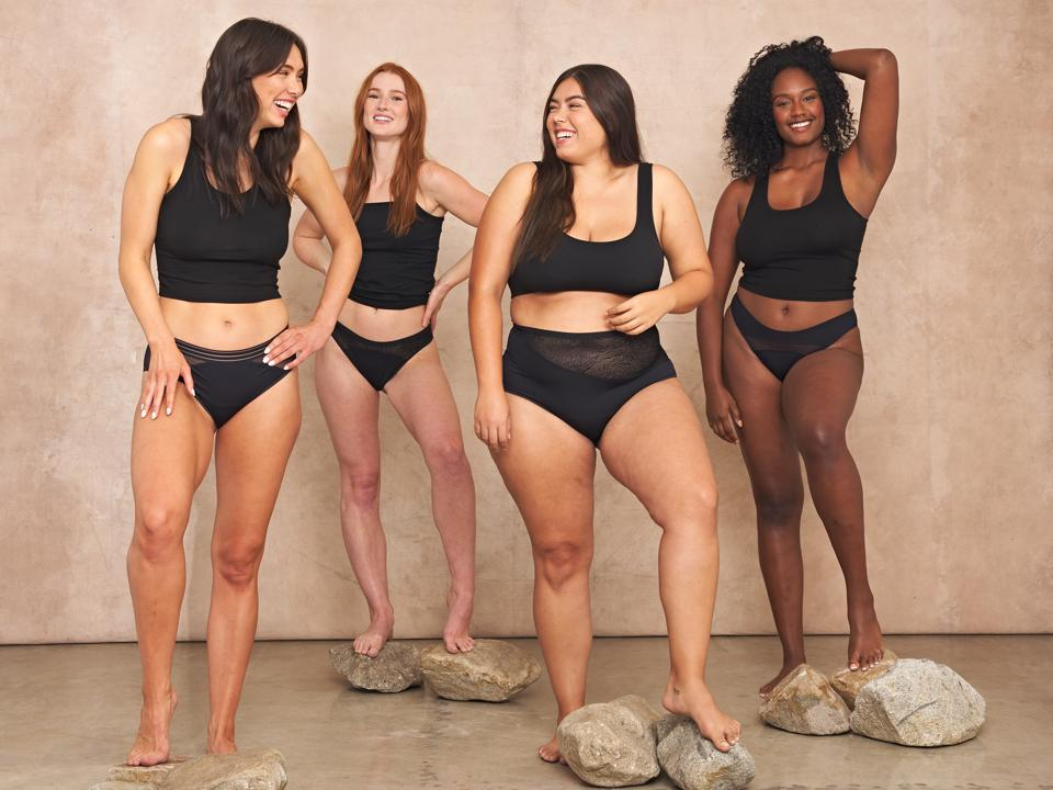 Four women of different sizes pose in black lingerie.