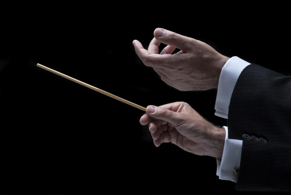 Cropped Hand Of Man Holding Stick Against Black Background