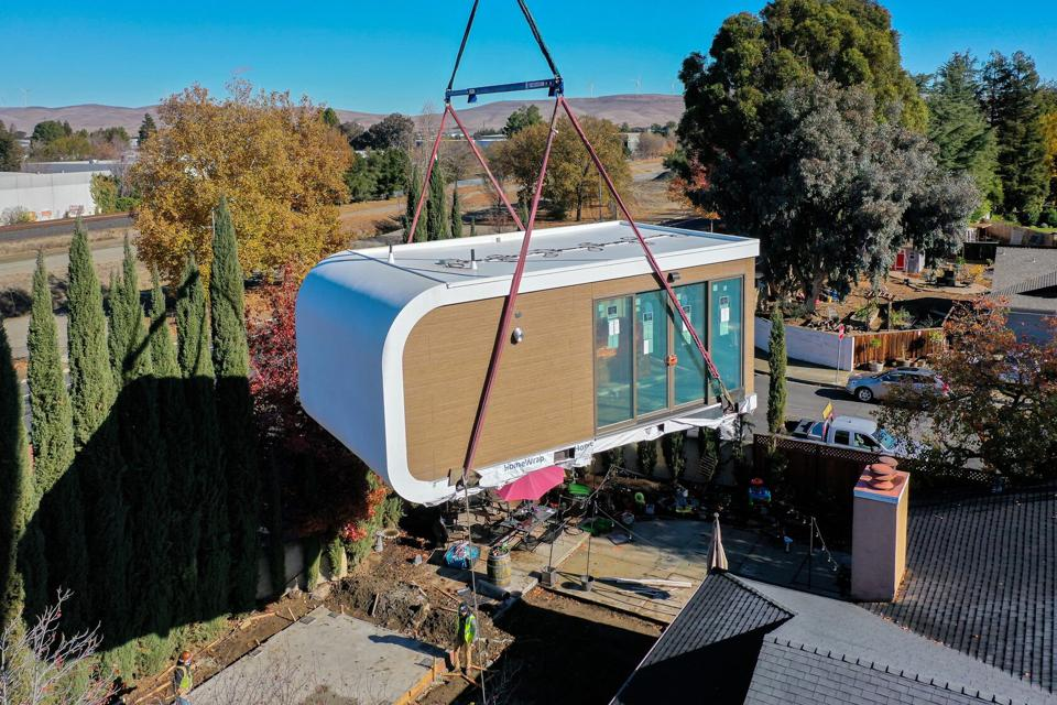 A 3D printed prefabricated building is placed on the ground by a large crane.