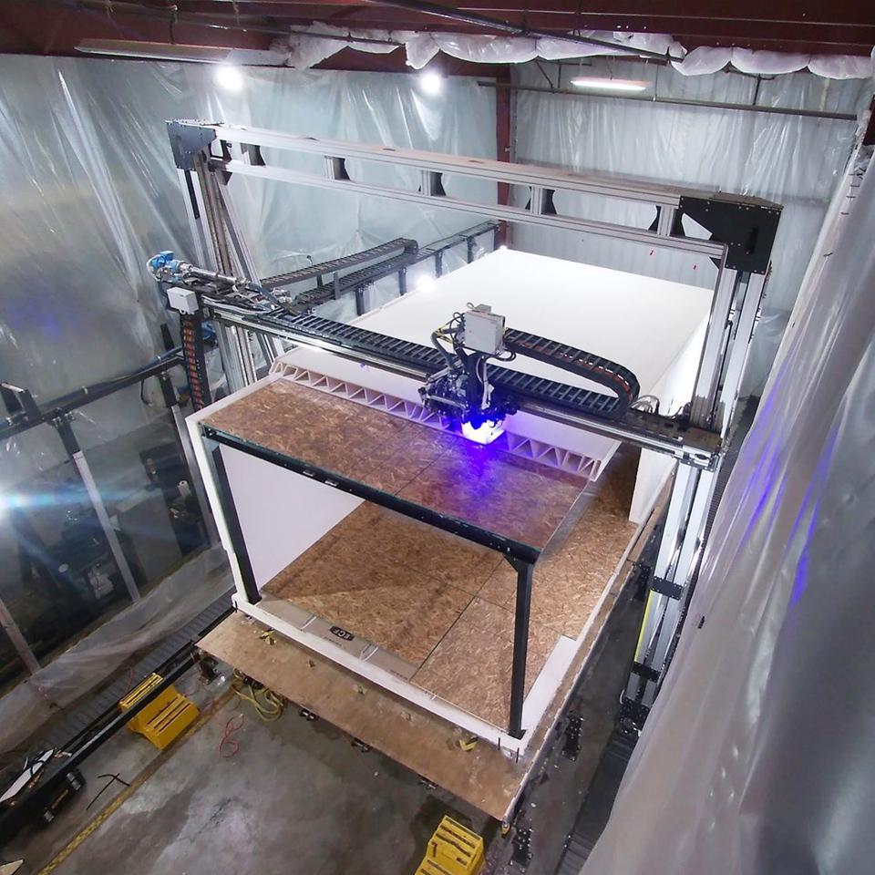 A large 3D printer works on the roof of a prefabricated structure.