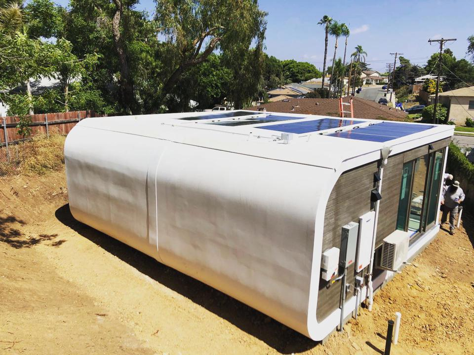 A prefabricated structure with solar panels on the roof is placed.