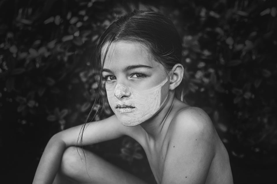 Sony World Photography Awards winner photo black and white young girl with face mask painted in her face.