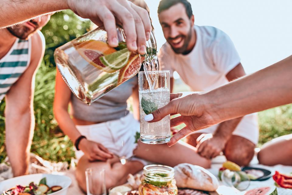 Guy pouring fresh homemade lemonade into glass of his girlfriend at outdoor party