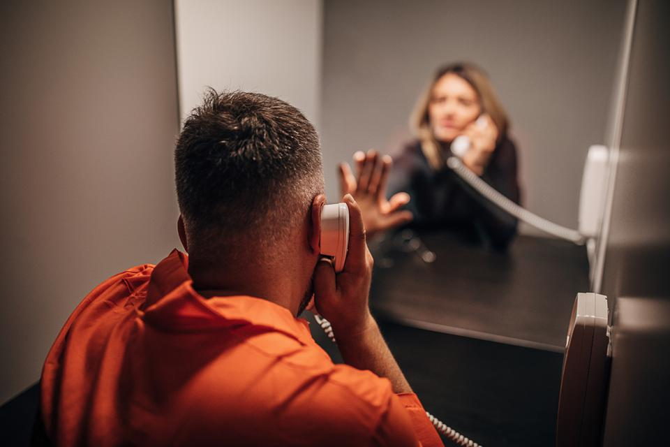 Young woman and her husband sitting in prison visiting room
