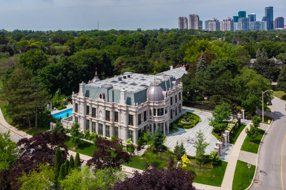 A beautiful mansion ensconced by forest with Toronto in  the background.