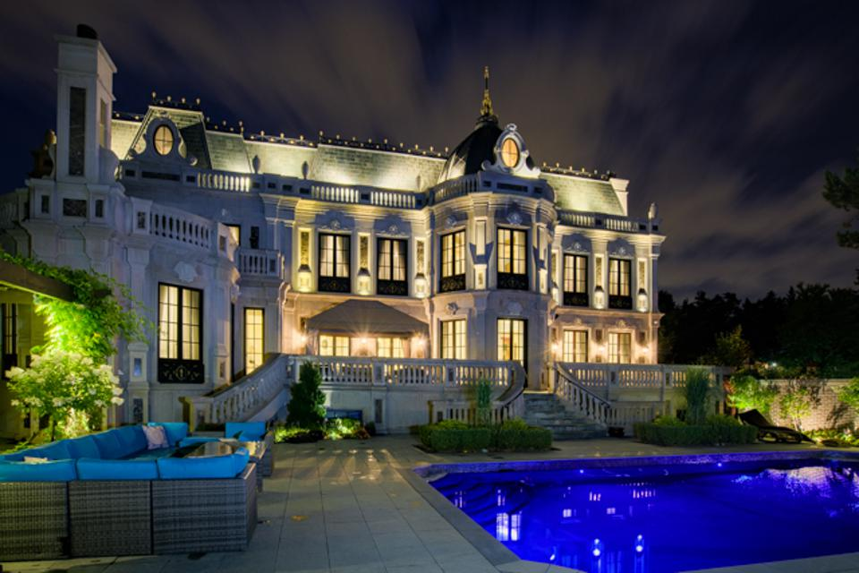 The exterior view of the chateau-style home with a pool and lounge area outside.