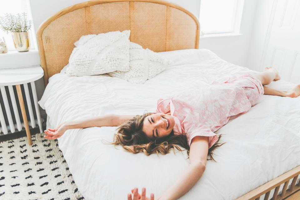 A woman lies in bed wearing Printfresh pajamas.