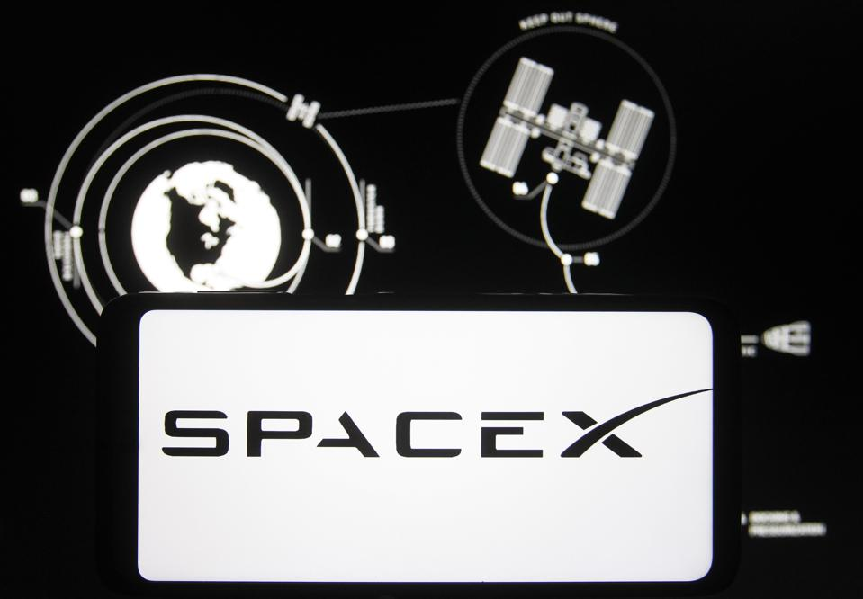 In this photo illustration a SpaceX logo seen displayed on a...