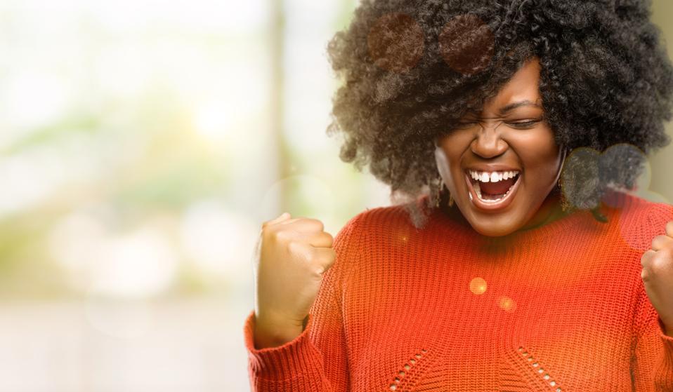 wanita yang bahagia dan bersemangat merayakan kesuksesan, kekuatan, energi, dan emosi positifnya. Merayakan pekerjaan baru dengan menyenangkan