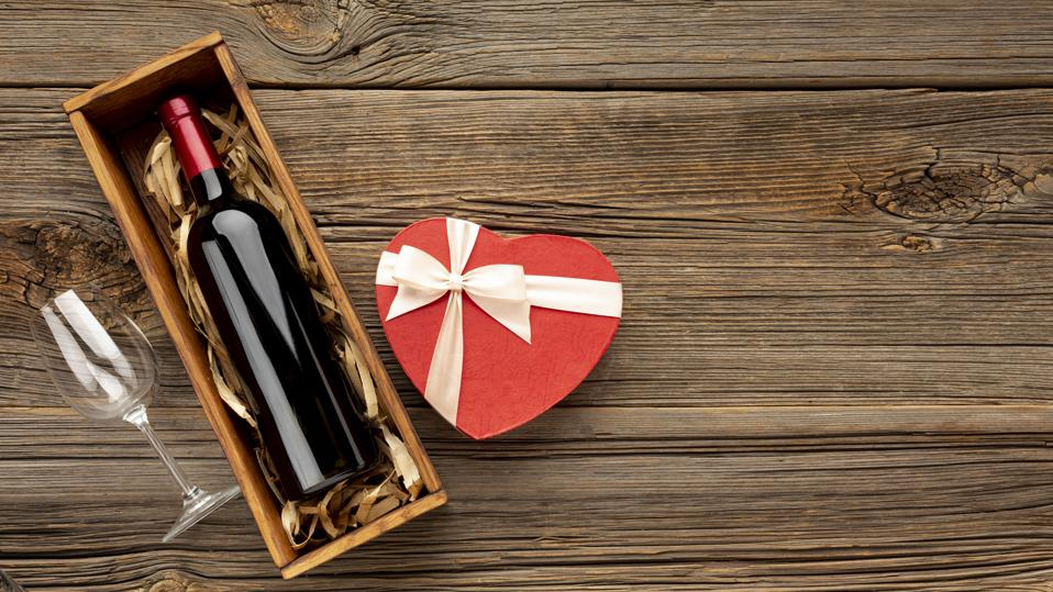 High Angle View Of Heart Shaped Gift Box With Wine Bottle On Table