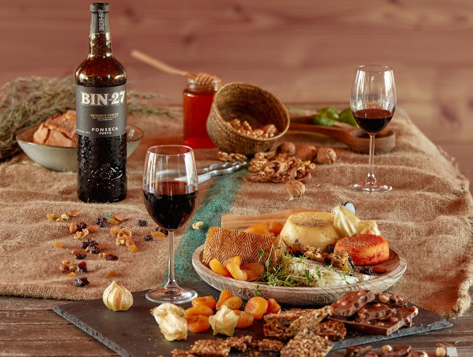 Bottle of Port with two glasses and a cheese board.