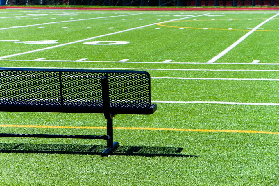 Empty Black Bench On Soccer Field During Sunny Day
