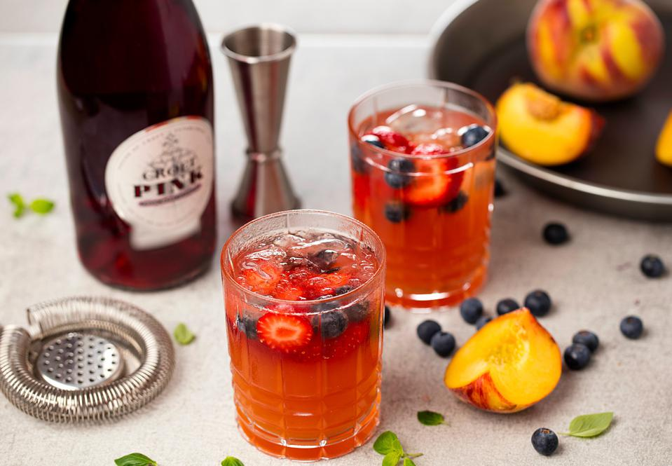 Bottle of Croft Pink and two cocktail glasses with mixed berries