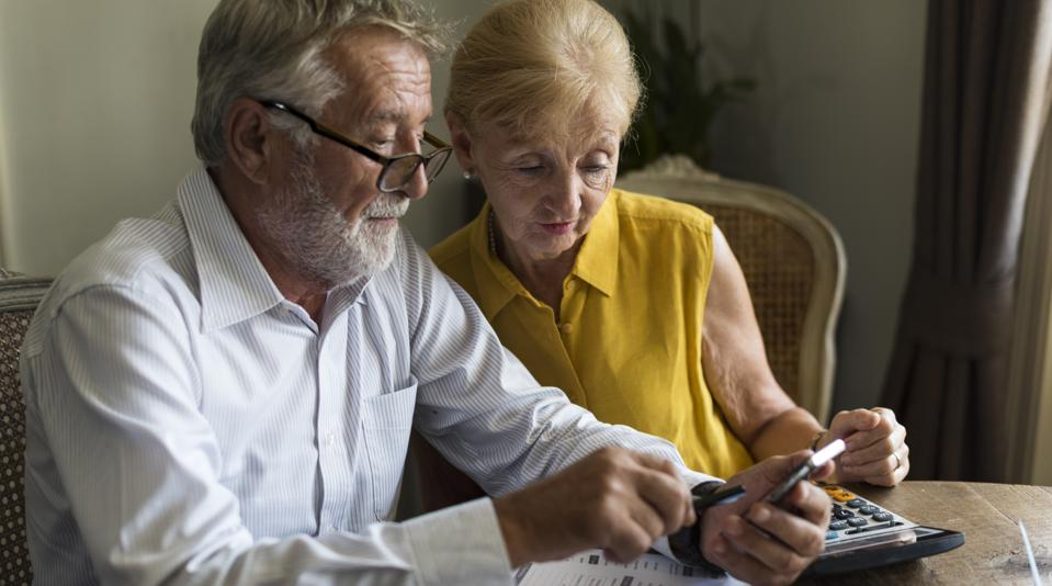 Older couple uses a calculator while filling out tax forms at a table.