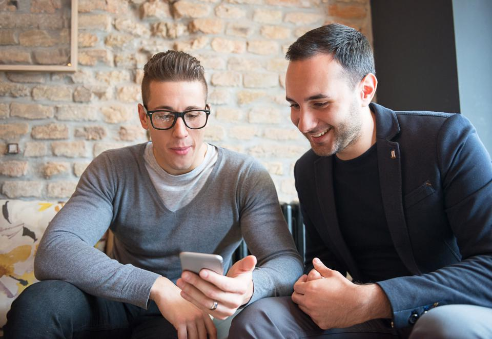 Two casual men using smartphone for communication and social networking