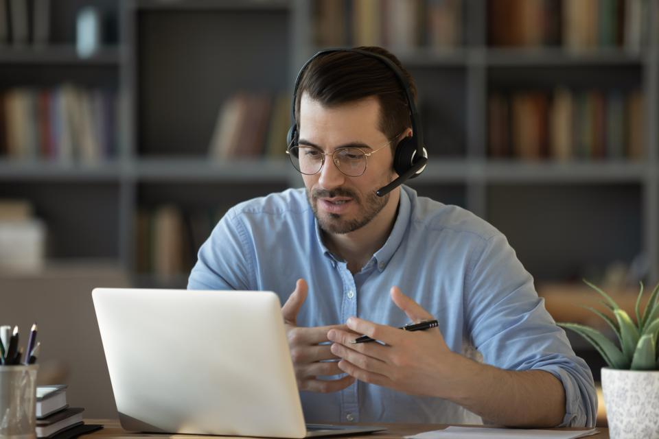 Confident man teacher wearing headset speaking, holding online lesson