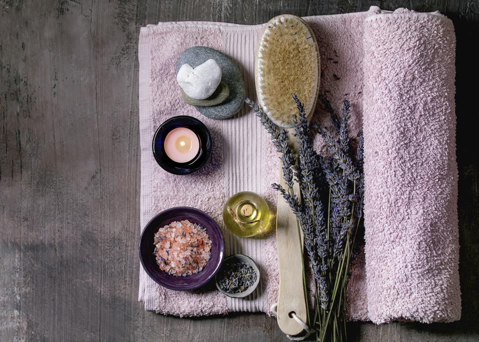 SPA concept. Flat lay of fresh and dry lavender flowers. essential oil. pink salt. stones as heart shape. aromatic candle on pink bath towel over textured background.