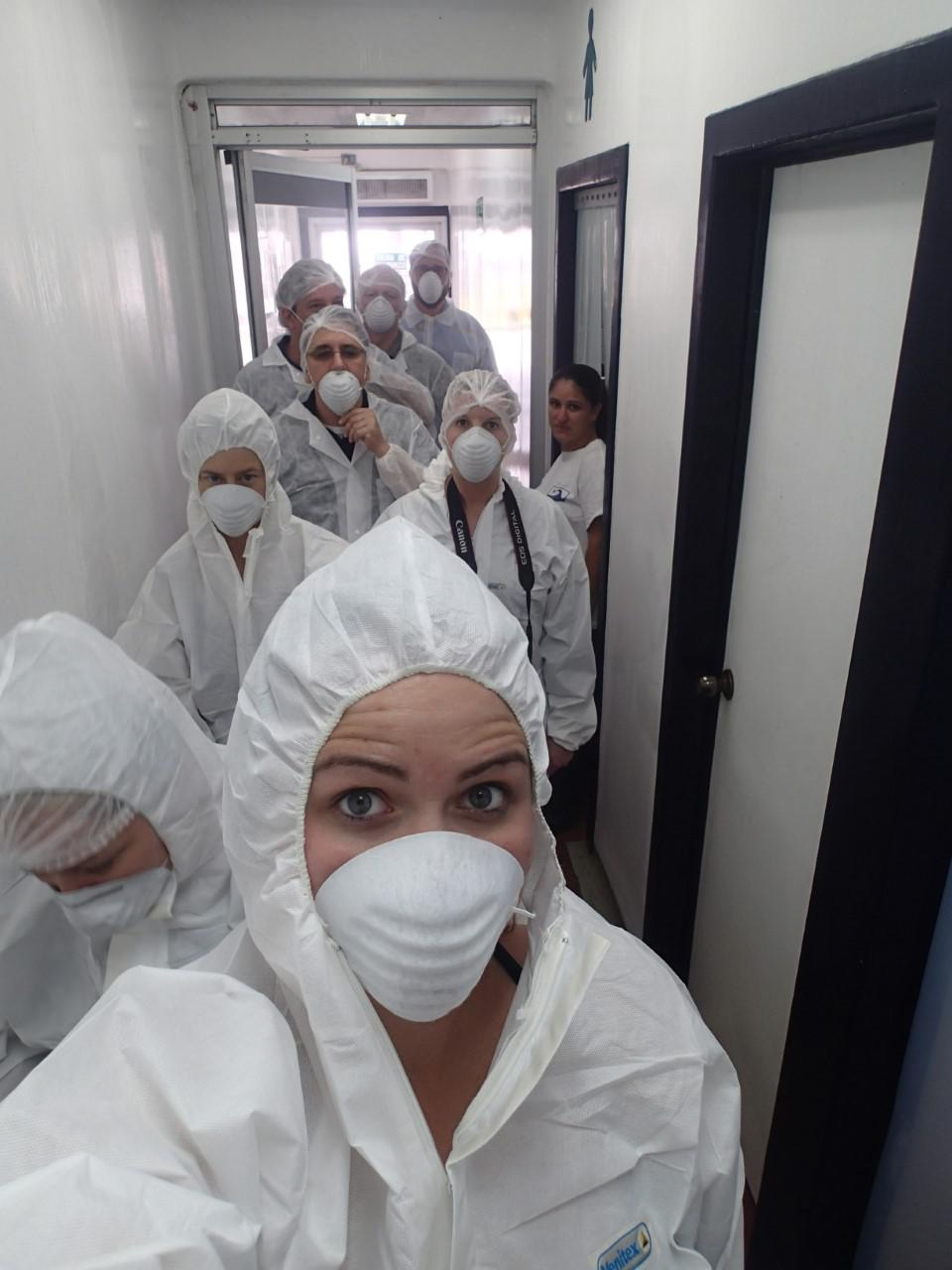 Woman in PPE and lab coat takes a selfie looking into the camera with 8 similarly-dressed individuals behind her in a hallway.
