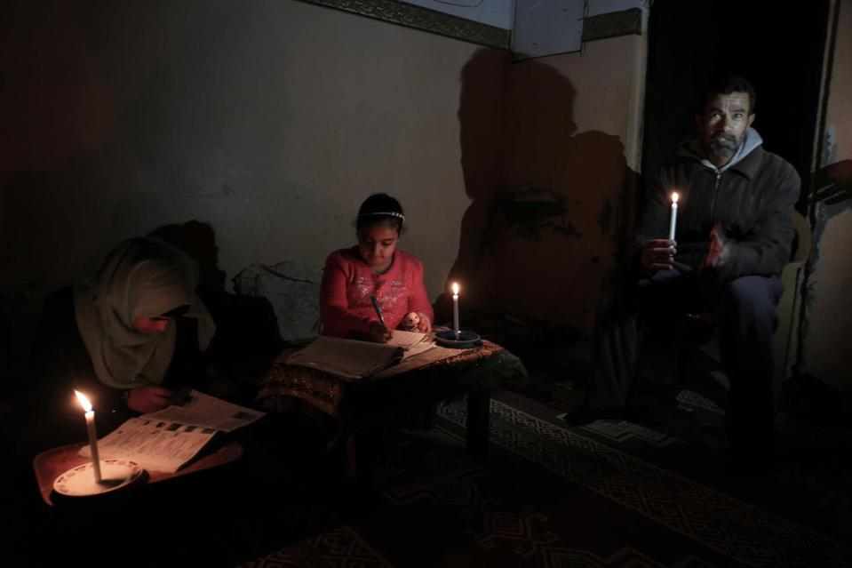 Palestinian girls study by candlelight in the southern Gaza Strip.
