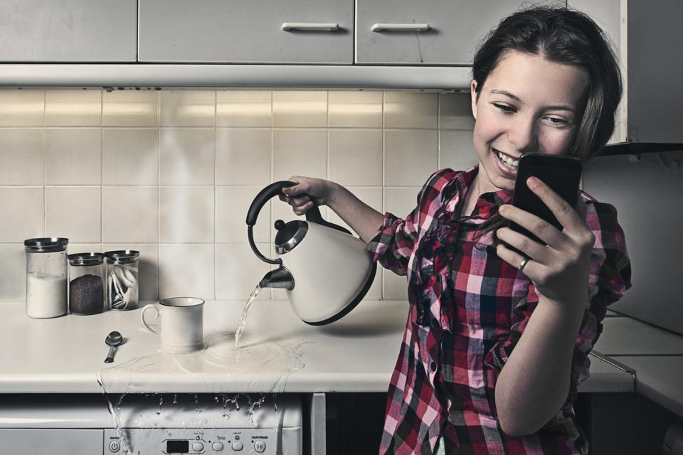 Woman on Phone whilst Pouring Kettle