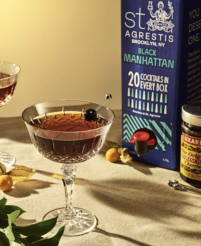 a cocktail glass filled with a manhattan from a box and luxardo cherries