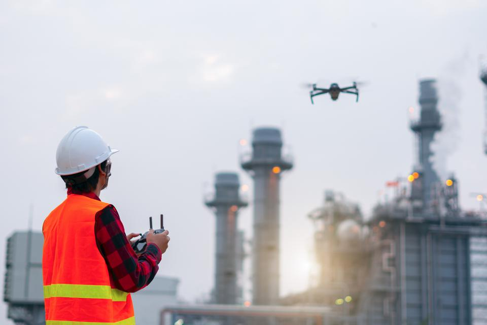 Young Engineer piloting drone at power plant . video surveillance or industrial inspection.