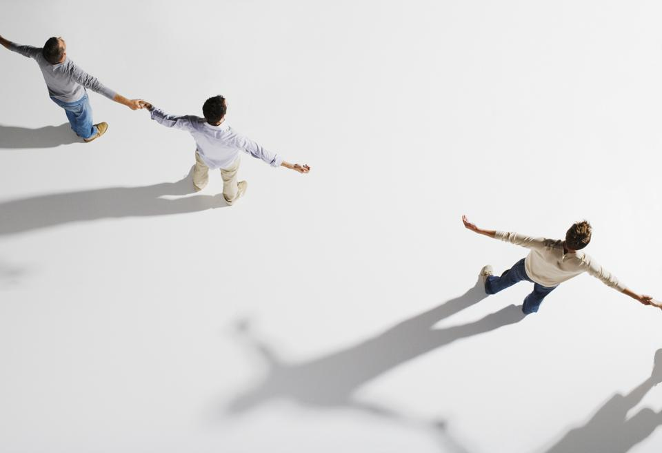 Two pairs of people holding hands, gap between pairs, overhead view