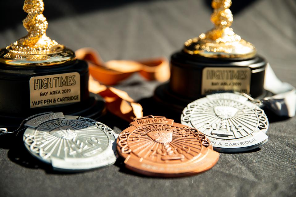 A closeup of High Times Cannabis Cup trophies and medals.