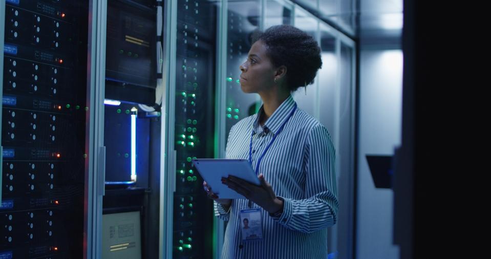 IT engineer standing among server racks in data center room