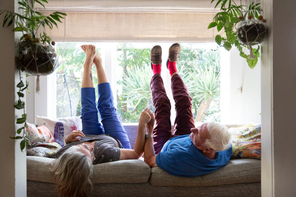 A senior couple lie on the sofa with their legs in the air