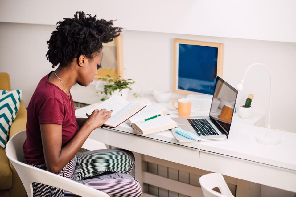Young African-American woman making business plans at her home office