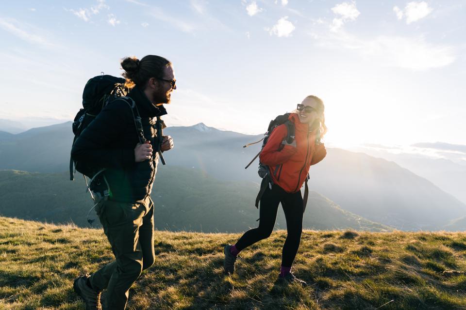 Couple hiking on mountain ridge at sunrise, smiling