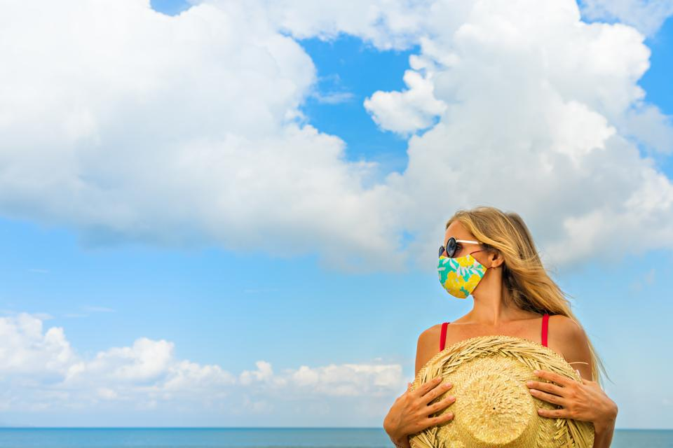 Young woman wearing sunglasses, face mask on tropical beach