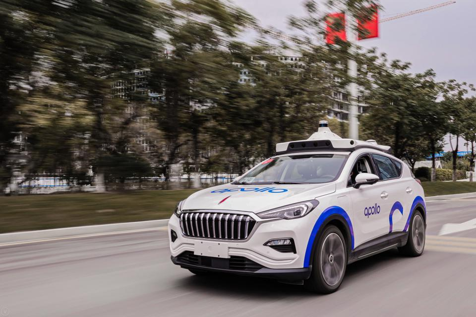 A white Apollo self-driving robotaxi SUV, with lidar and other equipment mounted on the roof, drives on a surface street in Guangzhou, China.