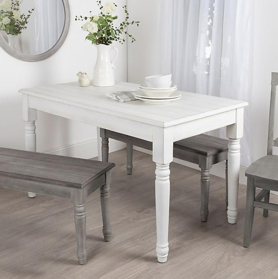 A white dining room table set up with gray benches and a gray chair