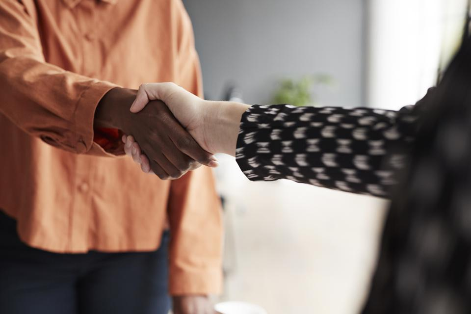 Business executives shaking hands at workplace