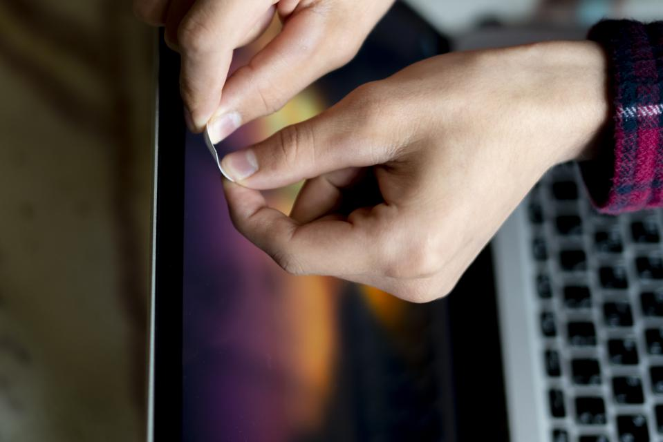 close up hand blocks the webcam with a white sticker tape