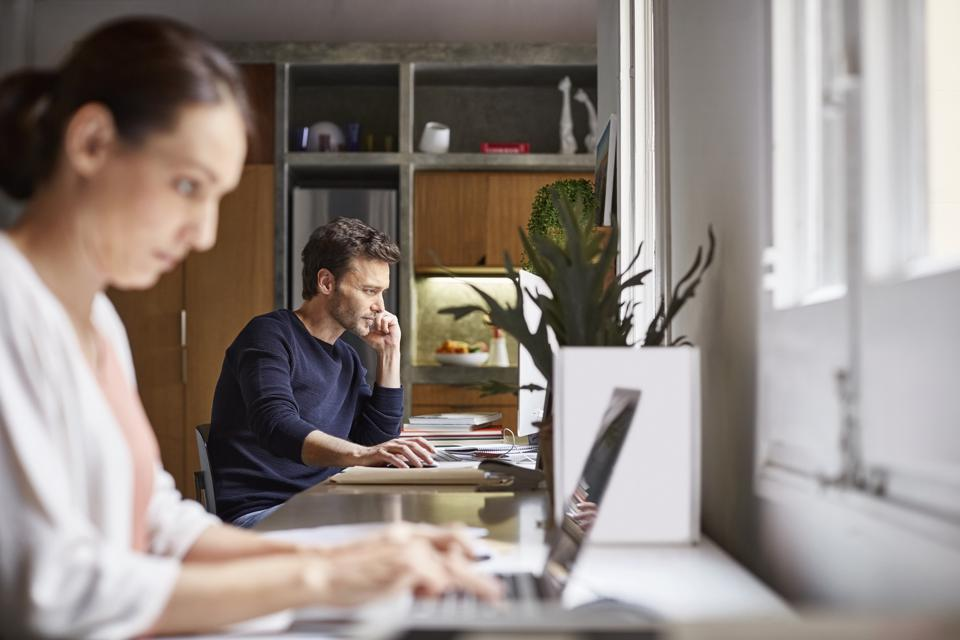 Mid adult business couple working at desk