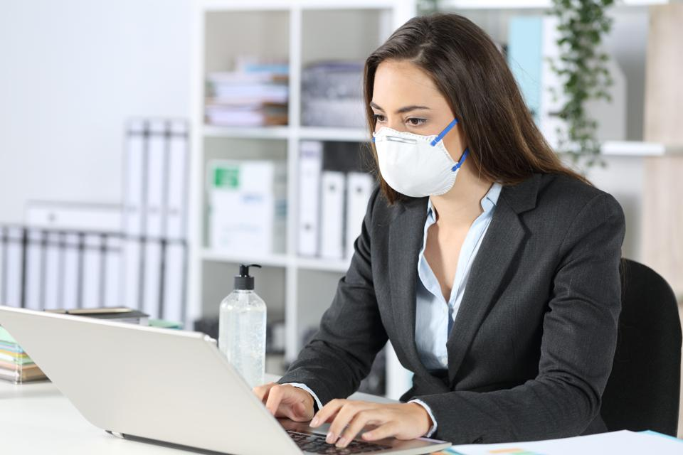 Executive wearing mask working on laptop at office