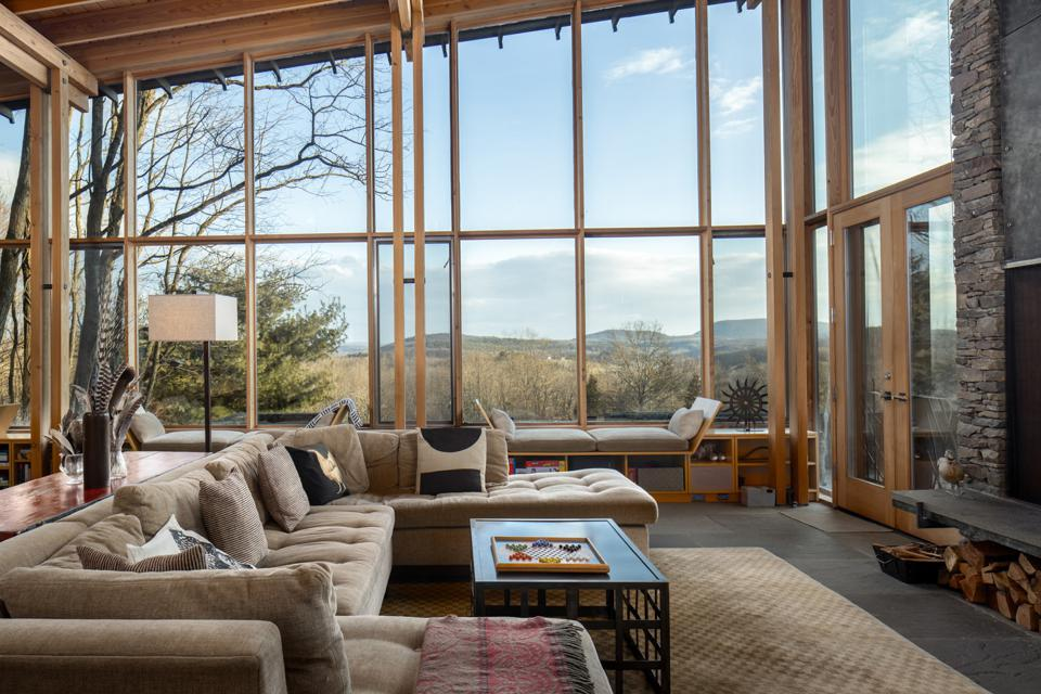 A living room with large glass windows overlooking mountains.
