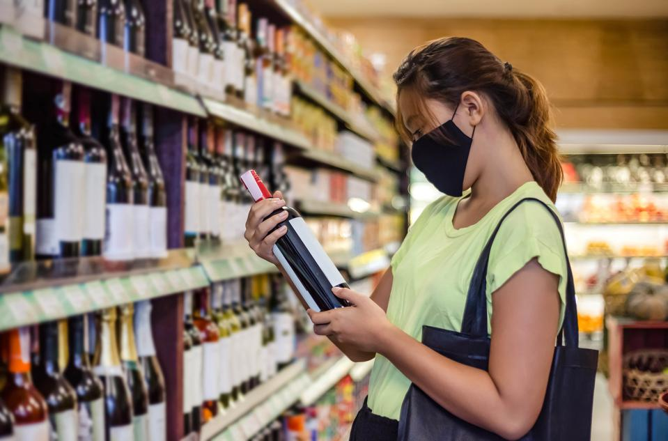 A woman wearing a mask shopping for wine.