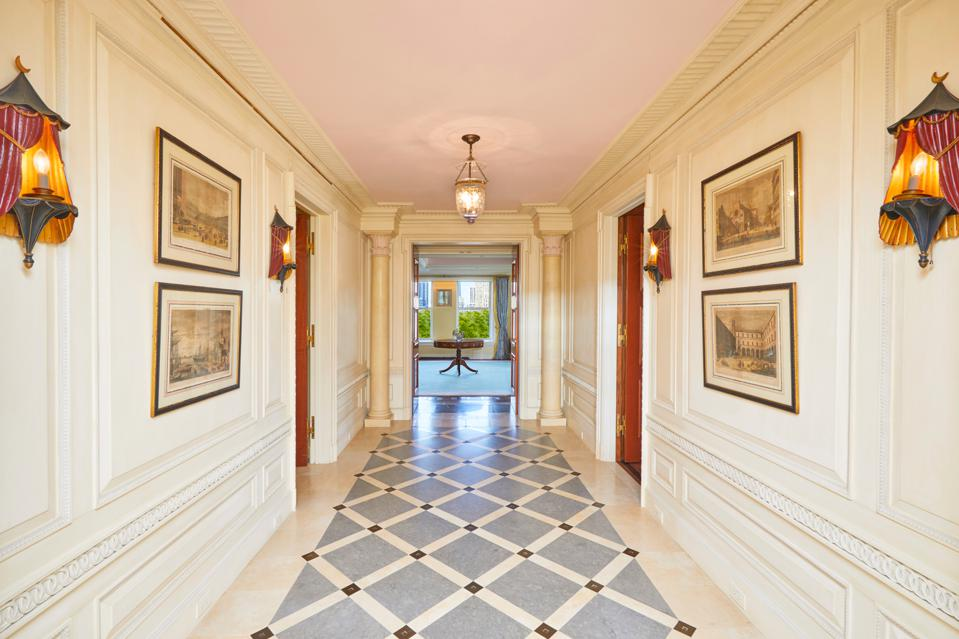 A long hallway leading to a living room.