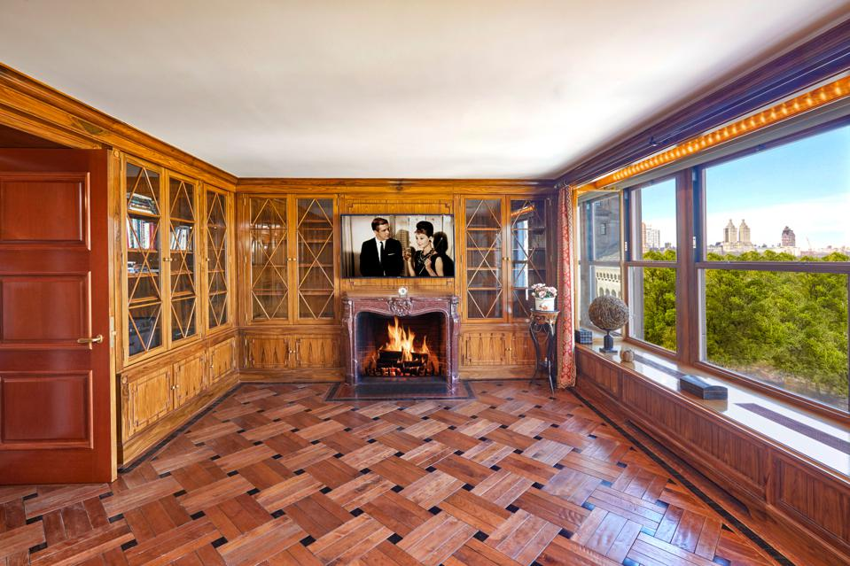 A wood-paneled room with a fireplace and a TV playing Breakfast At Tiffany's.