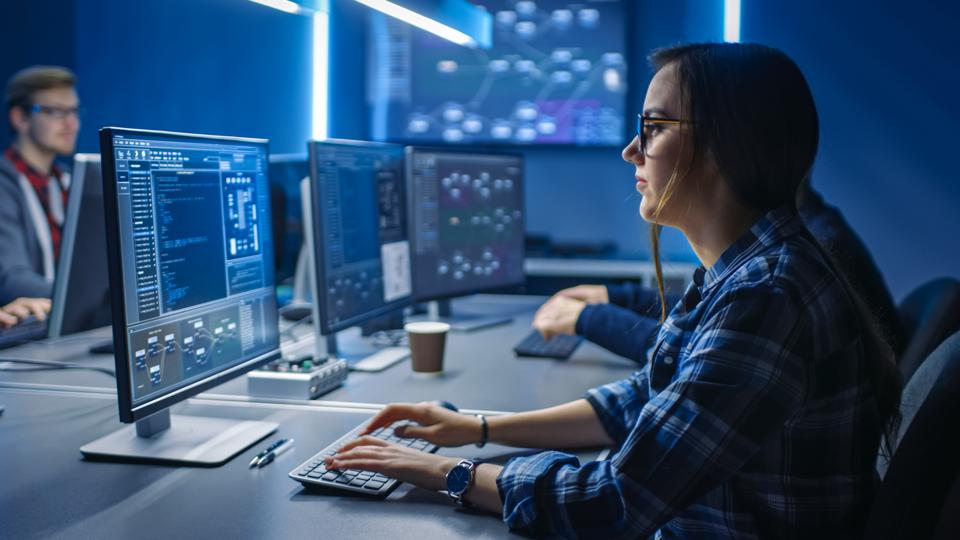 Smart Young Female IT Programer Working on Desktop Green Mock-up Screen Computer in Data Center System Control Room. Team of Young Professionals Programming Sophisticated Code