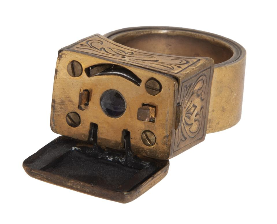 A brass pinky ring with a miniature camera built into a little box on top of it.