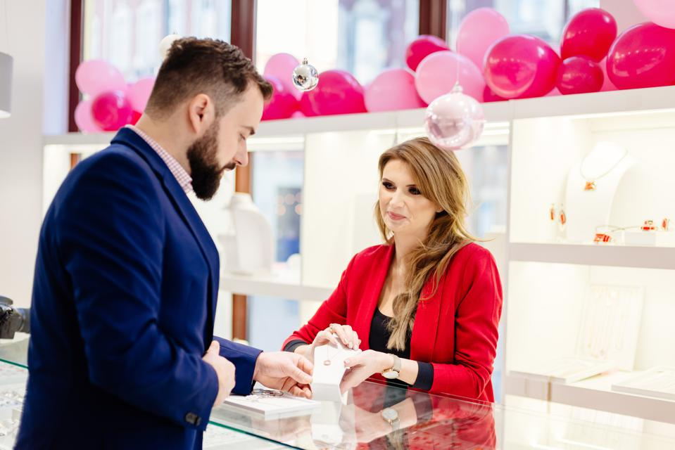 Man buying necklace in jewelry store.