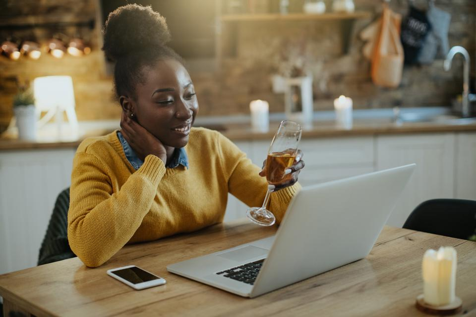Happy black woman toasting with Champagne during video call at home.
