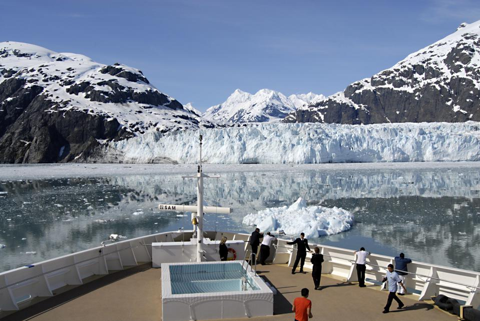 Tourists stand on the bow of a cruise ship to see Glacier Bay and the mountains in Alaska